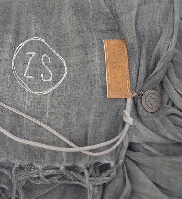 Zusss nonchalante sjaal. Deze fijne zachte basic sjaal van katoen combineer je gemakkelijk en heeft met nonchalante franjes. Afgewerkt met een contrasterend Zusss label. Draag deze sjaal binnen of buiten. Maat: 70x220cm. Materiaal: katoen.