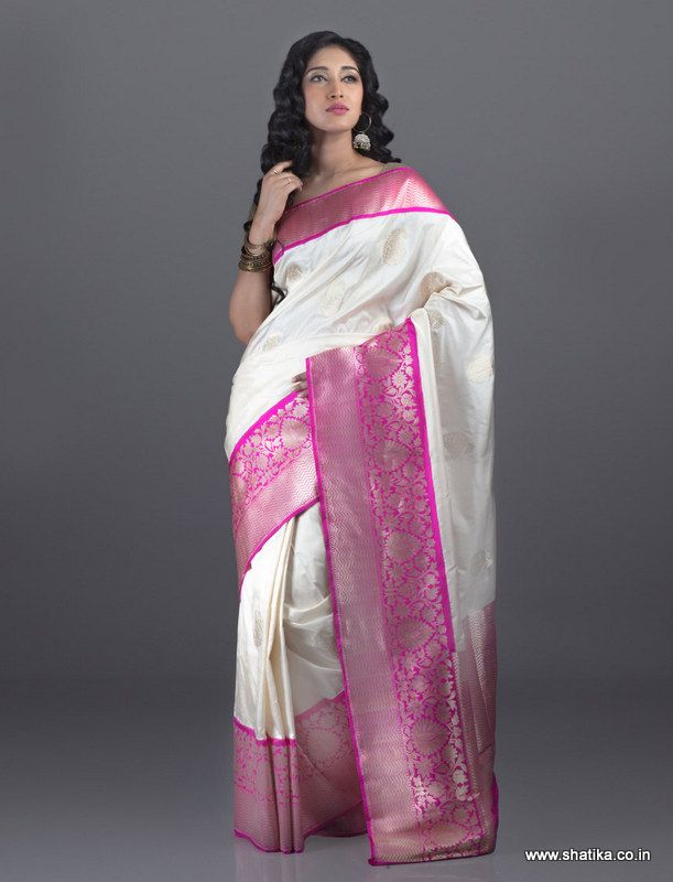 Sublime white color looks even more divine on a Khatan silk when beautifully contrasted with fiery pink on which silver brocade of real zari stands out magically. Made from the luxurious and celebrated Katan silk, these traditional Banarasi Silk Sarees Online are truly authentic and are world renowned as the finest real zari silk sarees and traditional wedding silk sarees.