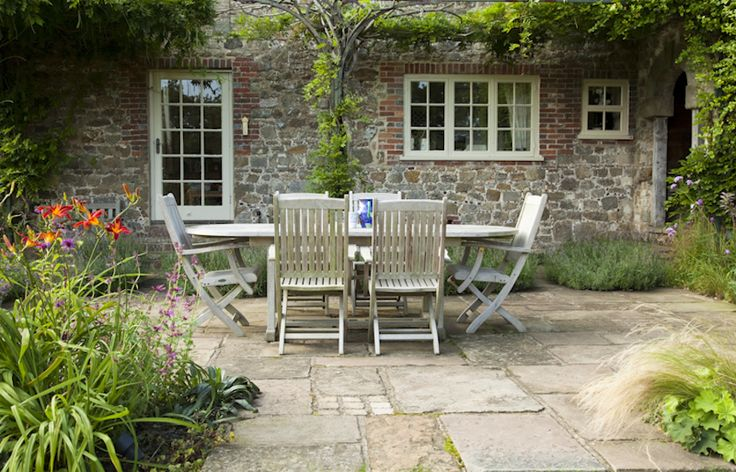 Classic English style. A York stone terrace studded with groups of sandstone setts is surrounded by country cottage plants to create a relax...