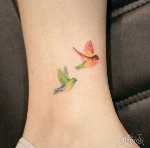 Colorful birds in flight on ankle by Tattooist River