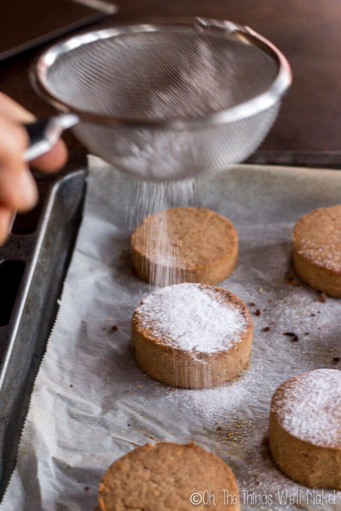 Sprinkling Just Baked Mantecados And Polvorones With Powdered Sugar