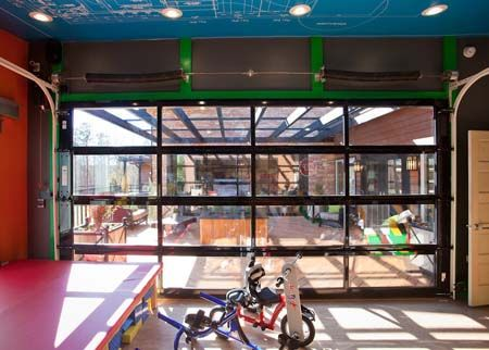 EMHE designers used Clopay Avante Collection glass garage doors as a moving wall of windows between the family's great room, the outdoor patio, and the new private therapy room built for the Williams' son Jacob, who suffers from Spina bifida, and his father Jeremy, who has ALS.