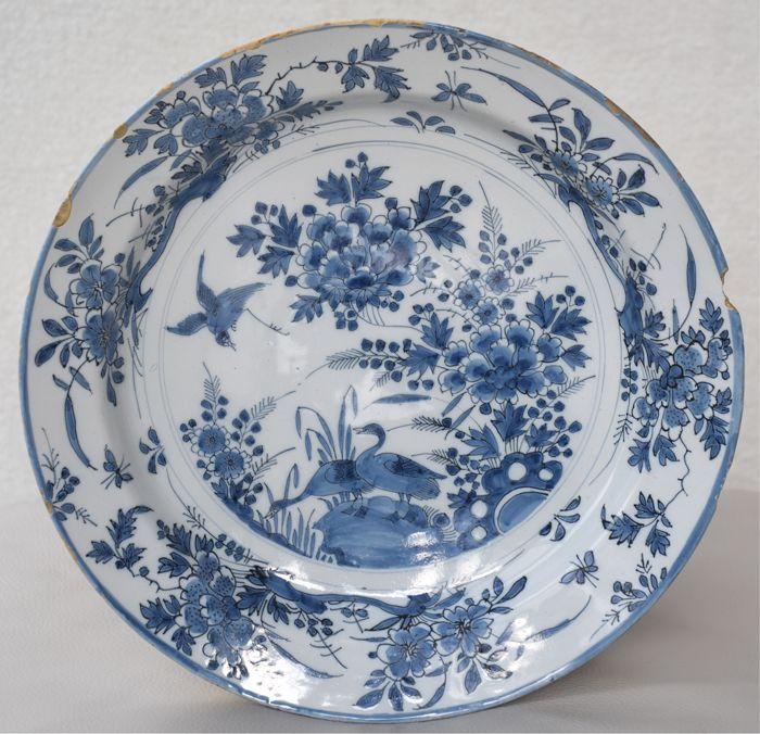 Een uitgebreide zachte gestemde hoge kwaliteit vroege Nederlandse Delft grote schotel ca. 1690  Grote 34 cm. schotel geschilderd met een zangvogel en twee pauwen (of ganzen) temidden van tweezaadlobbige planten. Clusters van anjer hoog gras en kleine insecten op de grens.Eventueel vervaardigd op De Grieksche A onder houder Adriaen Kocx. Men ziet veel overeenkomsten met zijn werk. De kleuren (een grijsachtig blauw en een zachte Toon donkerder blauw) de stijl en de objecten kunnen allemaal…