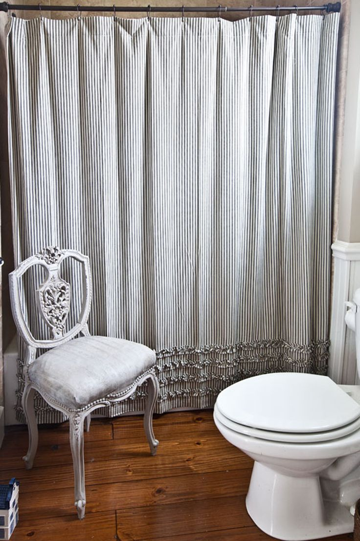 A Ticking Stripe Shower Curtain And Chair With A Matching