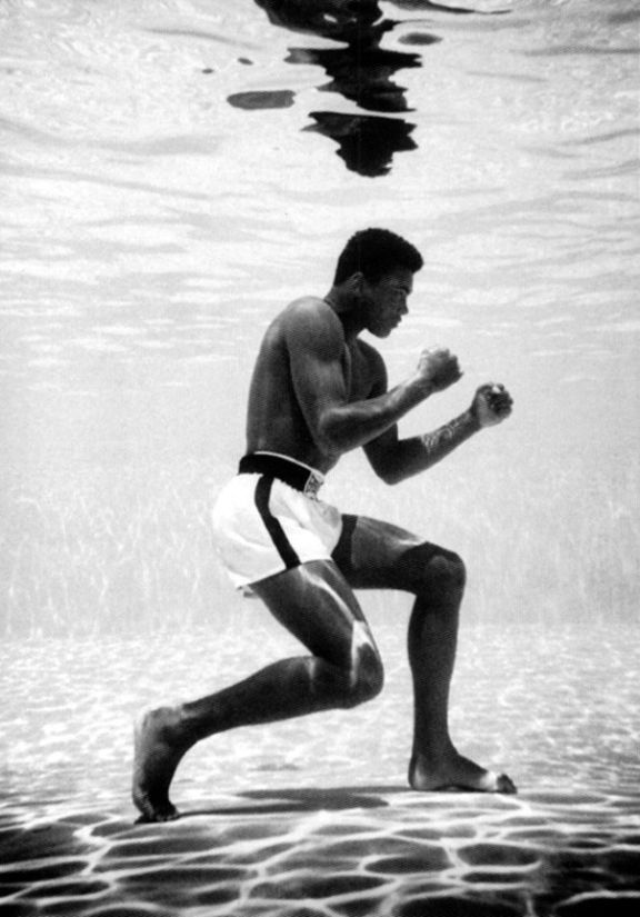 A stunning photo of Muhammad Ali in a boxing stance underwater while training in Miami, photographed by Flip Schulke, and featured in the book Muhammad Ali: The Birth of a Legend, Miami, 1961-1964.