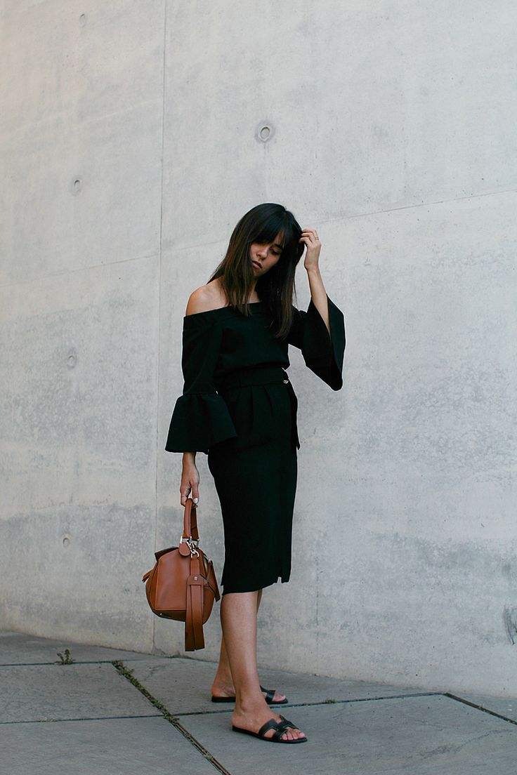 Nisi is wearing: Off-the-shoulder top with bell sleeves, midi skirt with slit, Hermès Oran sandals, Loewe Puzzle Bag