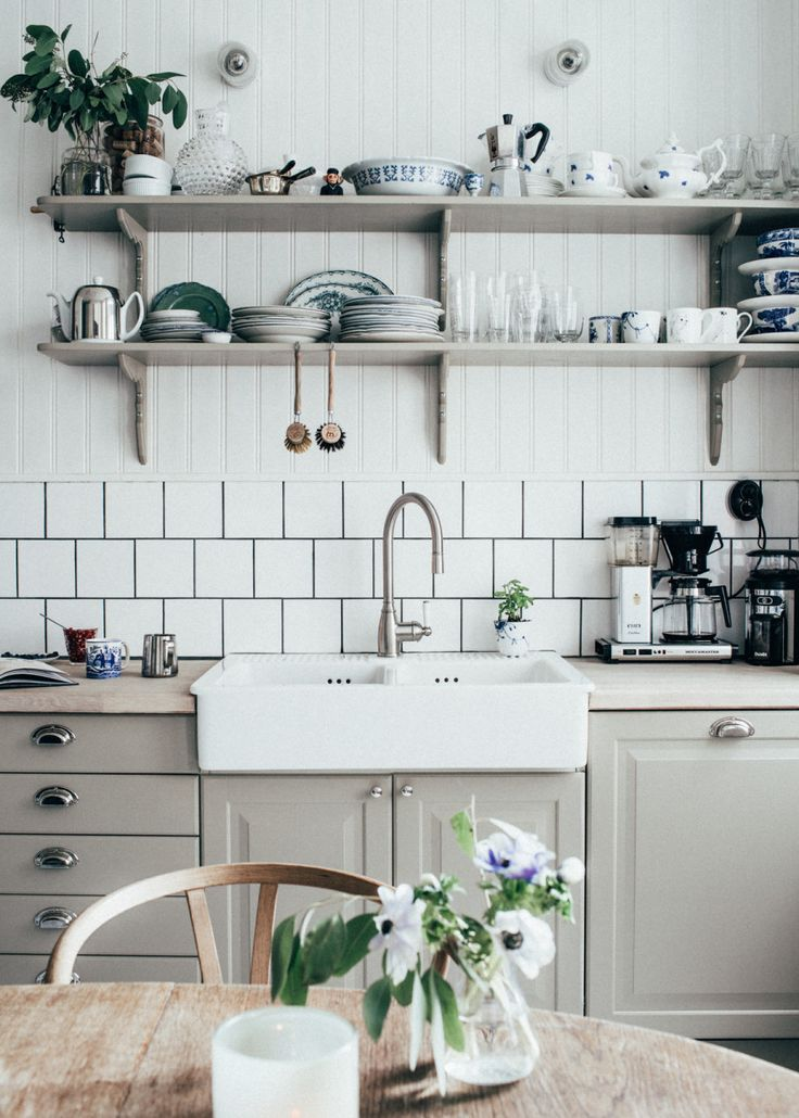 Open shelving stacked with mismatched crockery and mugs in a white and soft grey kitchen. Home of Johanna Bradford. Photo Kristin