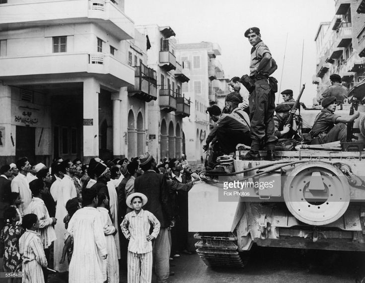 Egyptians crowd around a British tank in Port Said during the Suez Crisis, 12th November 1956.