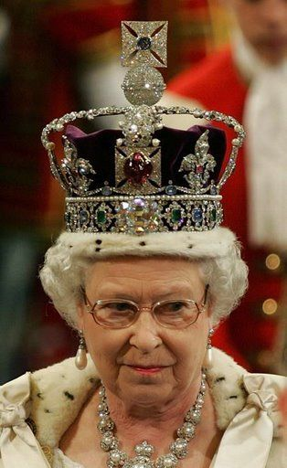 "HRM is wearing the Imperial State Crown of Great Britain, which incorporates the ""Black Prince's Ruby"", a 140ct. Badakhshan spinel. The crown was modified for Queen Elizabeth II prior to the 1953 coronation."
