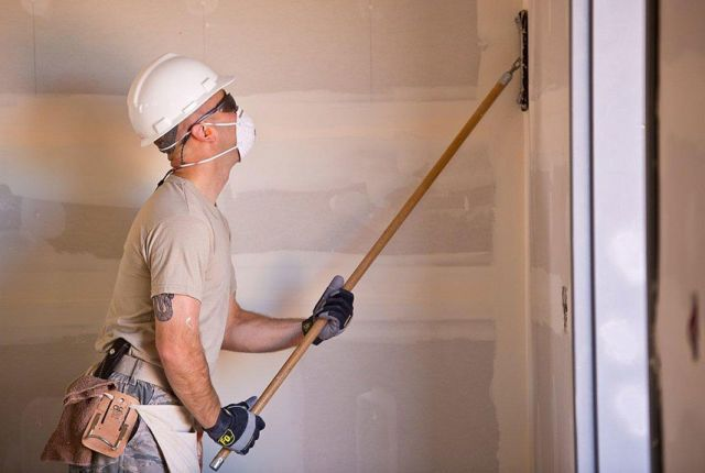 You have to start with a perfectly smooth surface to end up with perfectly painted walls or woodwork. One pro tells PM that sander would be a more fitting job title than painter since he spends so much time pushing sandpaper. Sanding levels outs spackle or joint-compound patches and flattens ridges around nail holes. Sanding also removes burrs and rough spots in your trim.  Sand the walls from the baseboard to the ceiling with fine grit sanding paper on a sanding pole. Then sand horizontally…