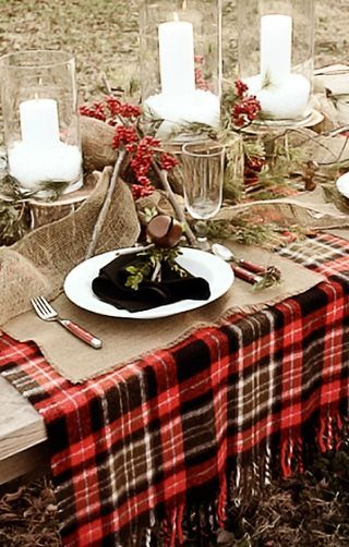 We love this rustic holiday table with a tartan blanket as the foundation, layered with burlap and  holly branches.