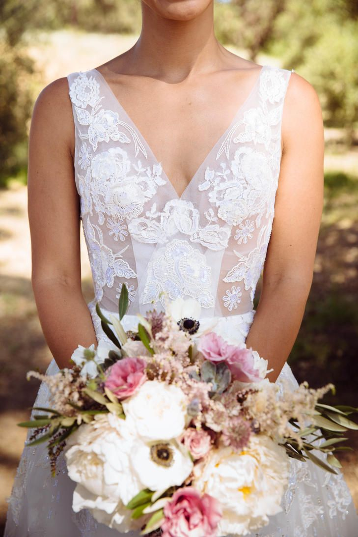 A unique bridal bouquet of lavender and dusty mauve flowers featuring anemone, peony, lisianthus, astilbe, olive and eucalyptus for this Campovida wedding. Beautiful Jorge Manuel dress. Flowers by Lily and Mint www.lilyandmint.com. Featured on The Knot.
