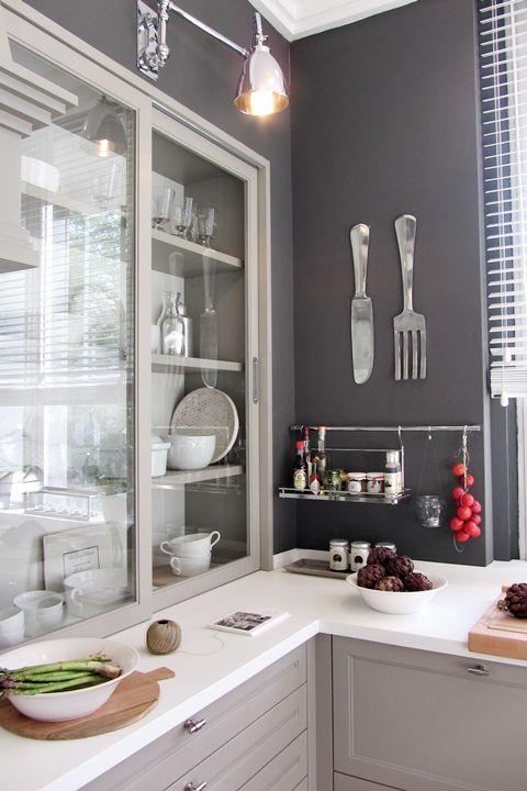 fabulosa!!! la lampara, el mueble tipo vitrina, los cubiertos como objetos decorativos en la pared, los barrales para dejar todo a mano, la mesada blanca, el color gris claro de los muebles y oscuro en la pared, el gran ventanal que le da esa increible luminosidad a la cocina y la hace sumamente calida!!!!!!!!