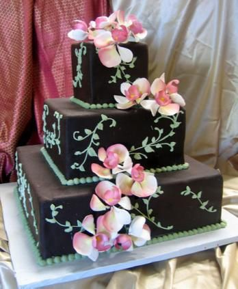 Romantic Chocolate - design # 57  3 square tiers with Chocolate Rolled Fondant and decorated with Vines and Sugar Orchids    From the Chocolate Wedding Cakes Catalog of The French Gourmet  We are open at 8:00am seven days a week.   Call us Toll Free: (800) 929-1984   Fax: (858) 488-1799    The French Gourmet  960 Turquoise Street, San Diego, CA 92109