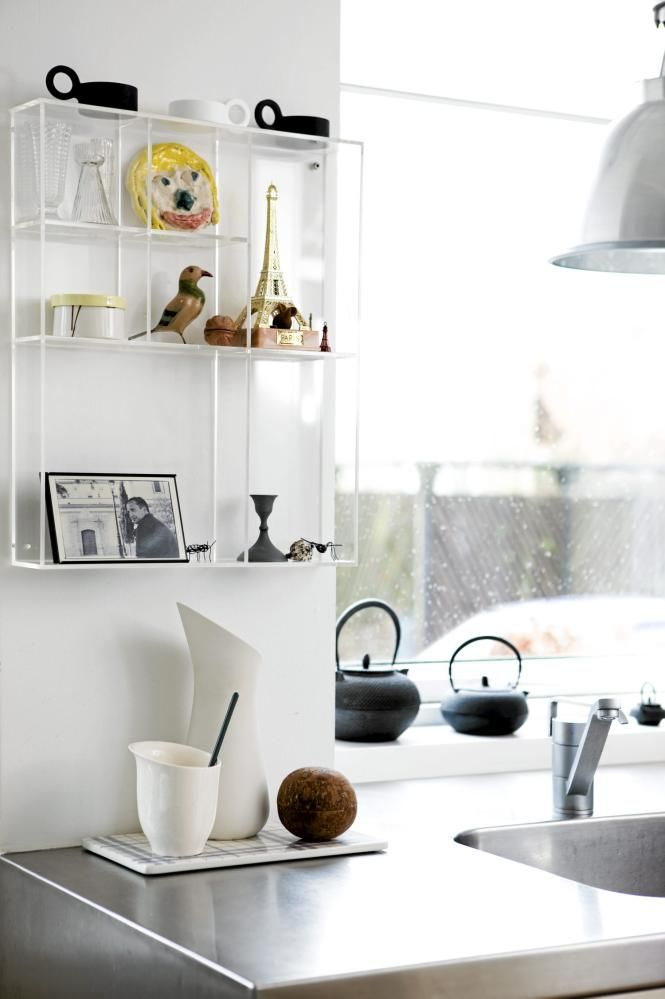 an airy, unique and personal display in a kitchen corner. gorgeous light streaming in.