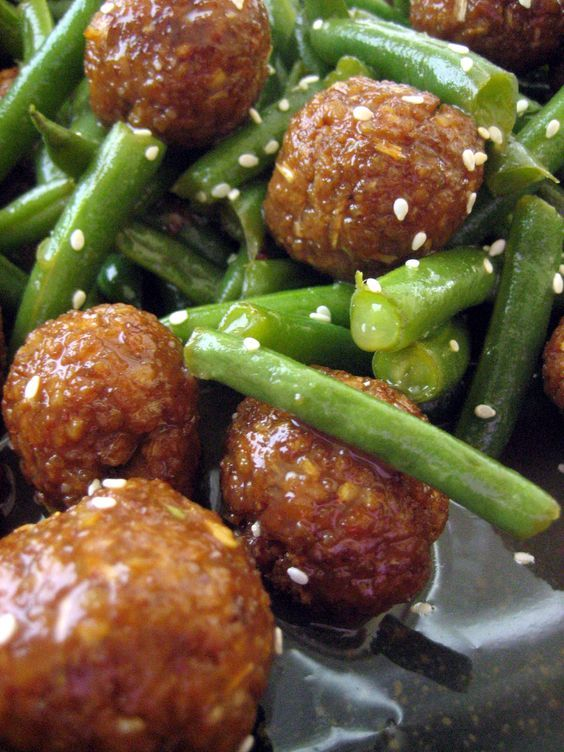 Thai Tempeh Balls with Green Beans: Tempeh is transformed into delectable balls spiced with leek, garlic, cilantro, chili, ginger and lime juice. These Thai spiced tempeh balls are balanced by a miso apple lemongrass glaze and finished with green beans and a sprinkling of sesame seeds.