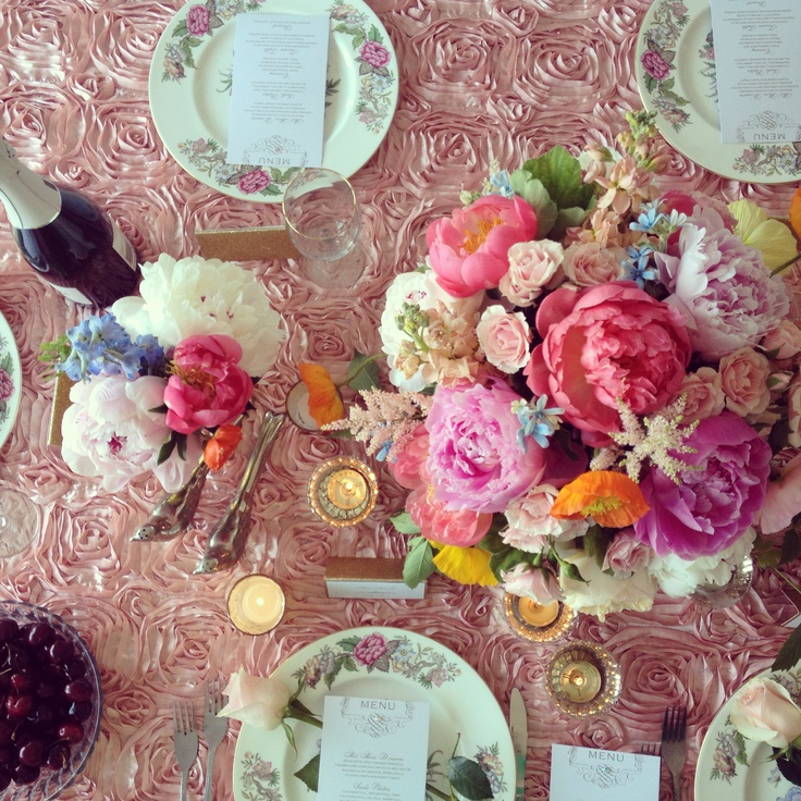 Pink linens, coral, pink and blush peonies, blue tweedia flowers, poppies, astilbes, with gold accents for wedding or garden party table