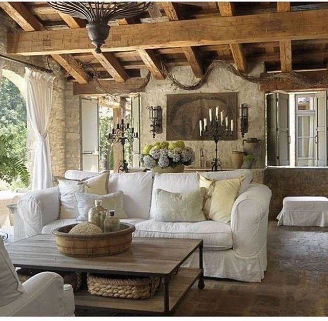 Love everything about this French country room - floors, feature brick wall, the candelabras and wall sconces, even the wooden bowl with the mixed items in it.