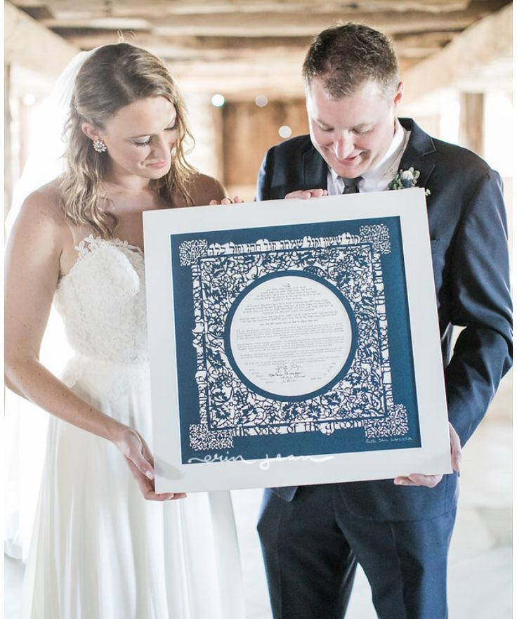 Couple holding Gefen Papercut Ketubah in Navy