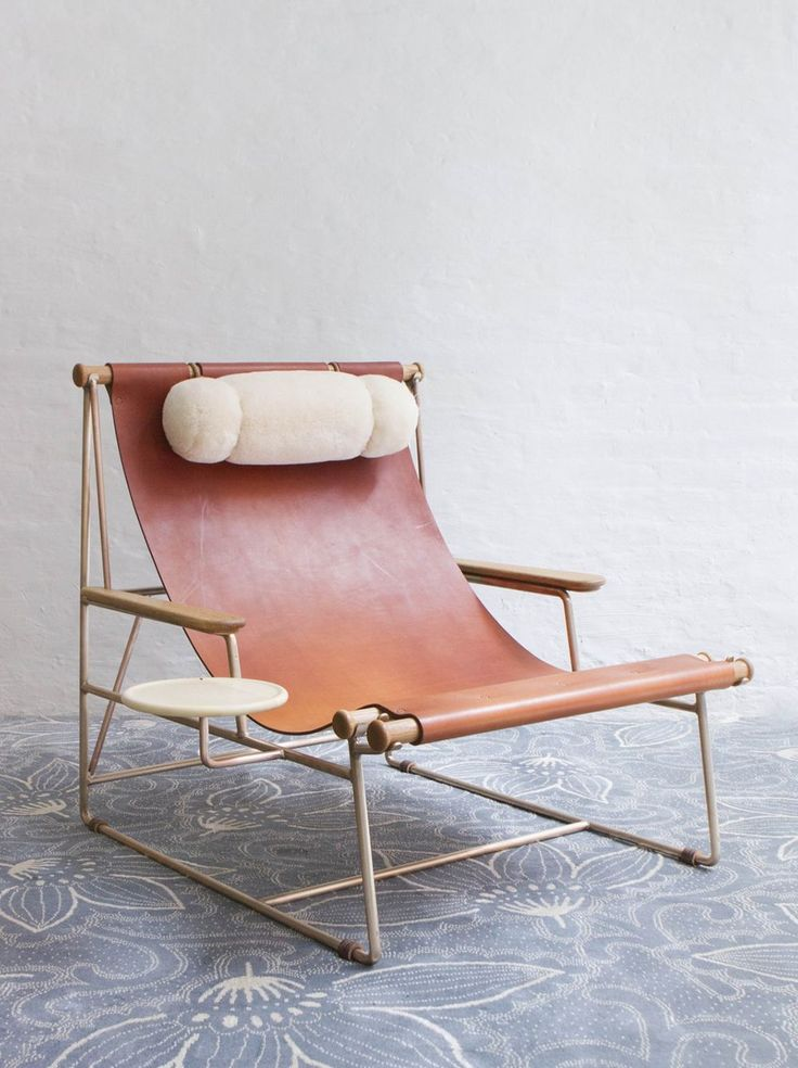 May I introduce you to the most stunningpiece of furnitureyou never knew you needed? This gorgeouschair, with its simple leather seat, bronzeframe, shearling pillow and wooden tray, is the brainchild of designer Tyler Hays of BDDW. It's a work of art -quite honestly, it is everything.