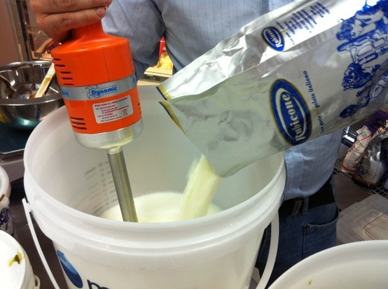 Giacomo pours the Rubicone Soft Yogurt Mild into the preparation.