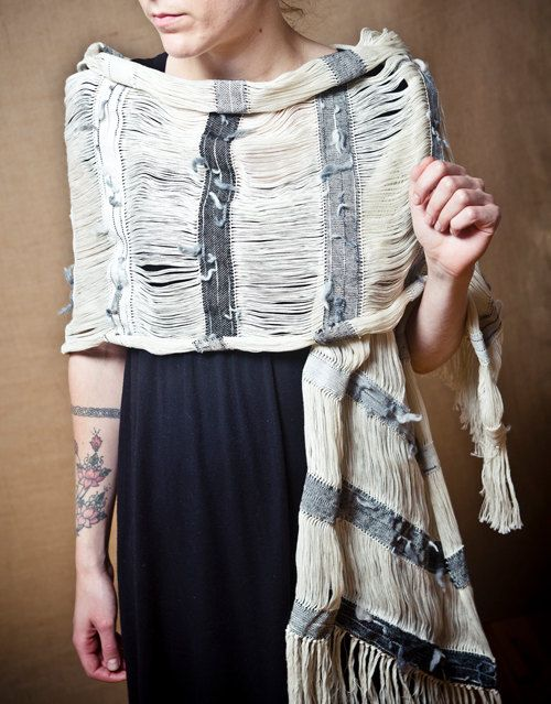 Handwoven shawl Arete with textured grey stripes. Its cotton warp is left unwoven at regular intervals giving unexpected shapes when parts of the