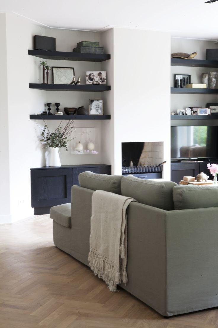 Eenvoudige schouw met robuuste planken aan beide zijden. Onderop kastjes, tv rechts naast de schouw aan beugel aan de muur, niet boven de haard