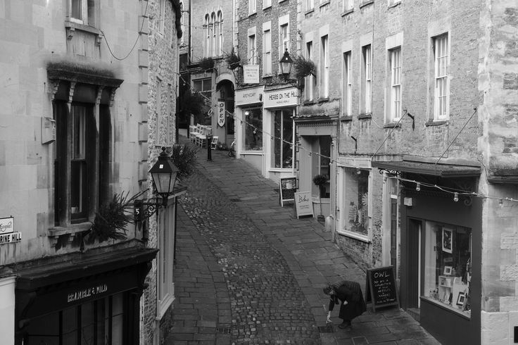 https://flic.kr/p/QyLkRb | Catherine Hill | Something a bit different to start the New Year, a new picture of Catherine Hillin Frome which looks like it was taken years ago. Taken from upstairs in the newly opened Sam's Kitchen, which has gorgeous views of the town. Had to wait a while for the street to clear, just as this lady came out to pour the remains of her drink down the drain!