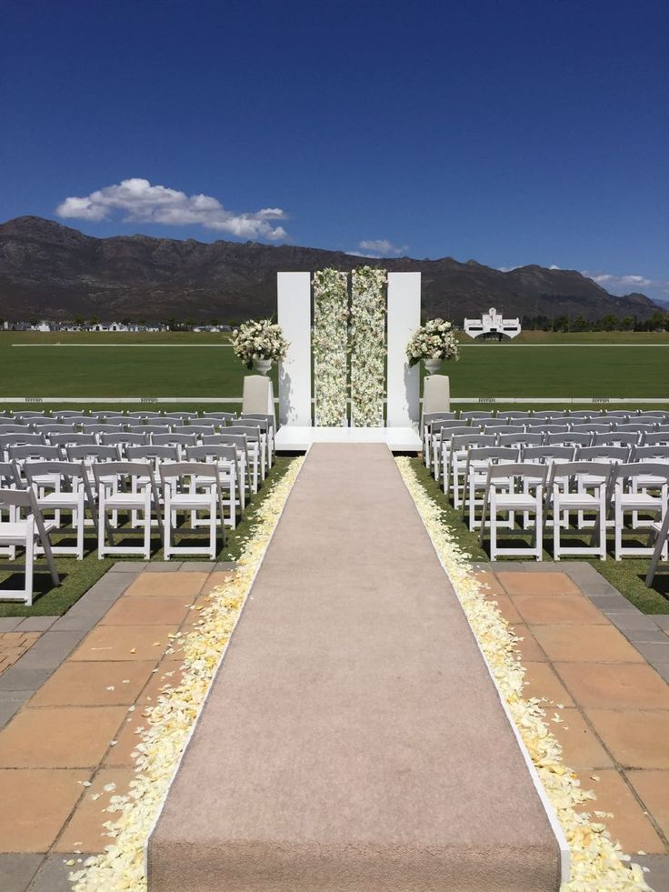 OKASIE | Raised aisle with carpet runner leading up to dramatic floral panels & floral masses
