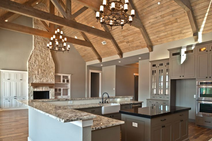stone fireplace vaulted wood ceiling large light fixtures open concept gray/taupe cabinets