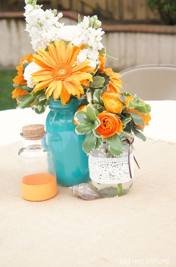 a beachy surfer dude baby shower - floral centerpieces in mason jars and lace wrapped vases give a more homespun feel that keeps to the party theme.