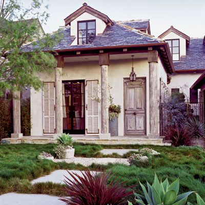 Weathered log columns add age and personality to this new house.