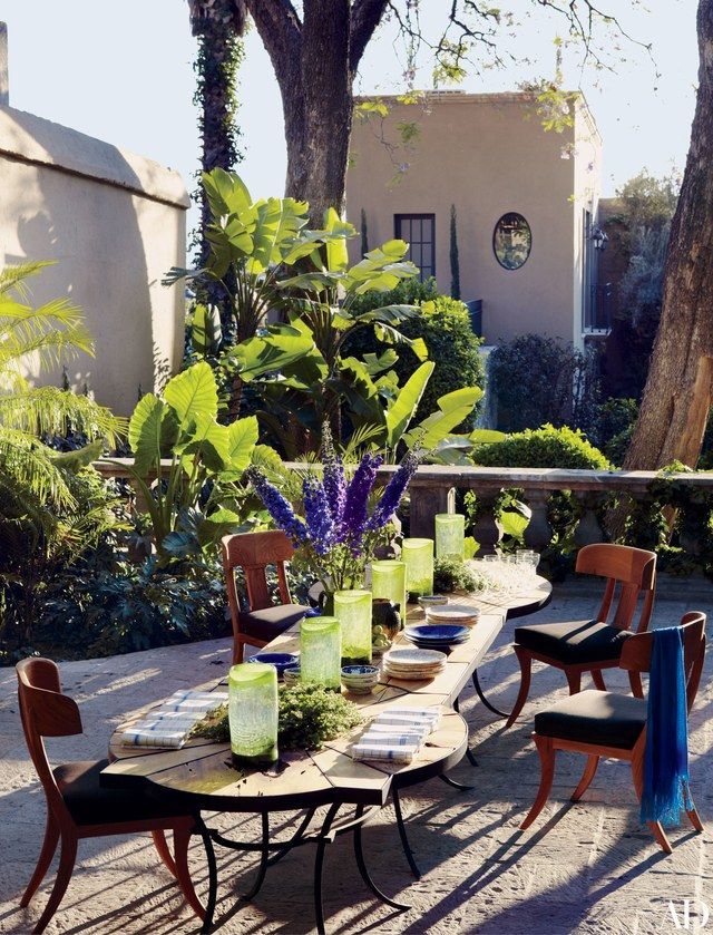 The tables on the dining terrace of Andrew Fisher and Jeffry Weisman's San Miguel de Allende, Mexico, retreat are by Fisher Weisman; the Michael Taylor Designs chairs are covered in a Sunbrella fabric. | archdigest.com