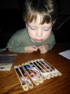 Toddler puzzles using large Popsicle sticks and family photos.