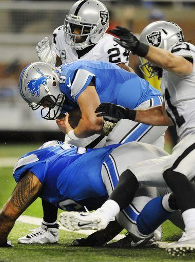 Lions quarterback Matthew Stafford barrels over teammate