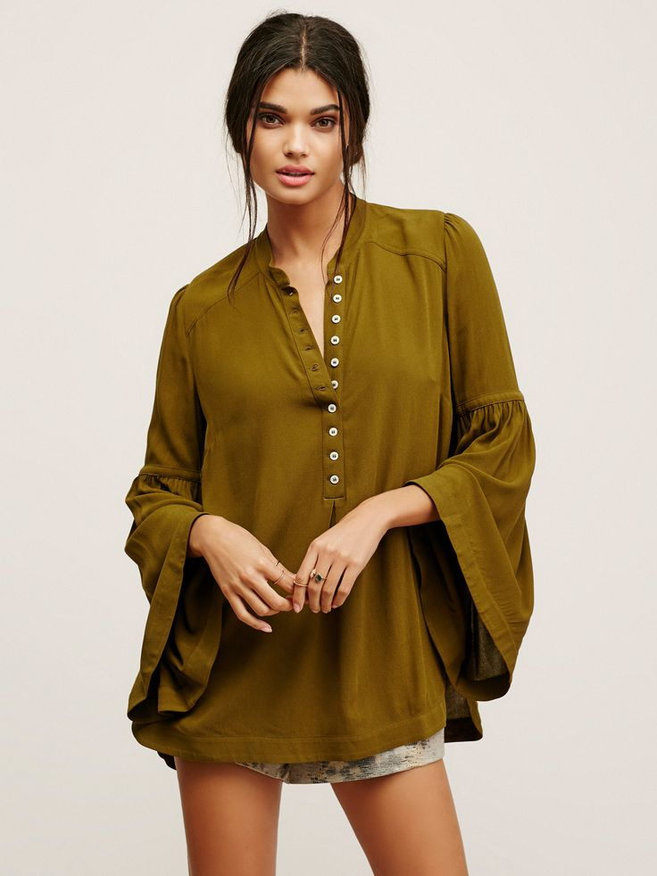 Femme tunic with a button placket featuring subtle pleating. Statement wide bell sleeves and a rounded hem with side vents and a high low hem.