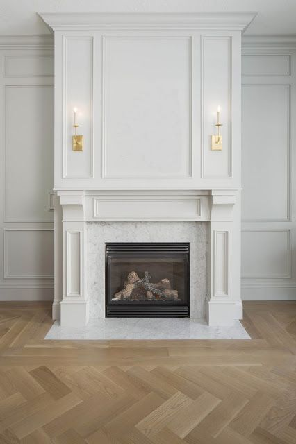 visual comfort sconces, gray wainscot room, herringbone floors, carrara marble fireplace surround via WHITE + GOLD