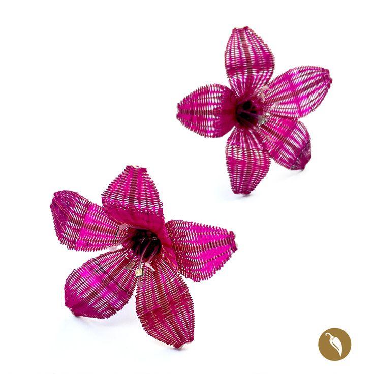 Añañuca es el nombre de la flor construida en crin que se destaca en estos hermosos aros. La flor tejida en crin se sostiene sobre una media bola de plata. Dos de sus pistilos son de plata, lo cual otorga más brillo a la flor. Monocoes la precursora de la incorporación de la artesanía en crin en la joyería contemporánea. La diseñadora rescata este patrimonio inmaterial y lo incorpora en la joyería, fusionando el diseño y la artesanía.  Autor:Monoco Colección: Flores Rari Materiales: C...