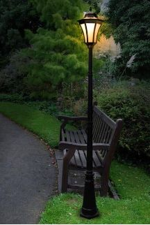 A bench seat and lamp along side the castle driveway.