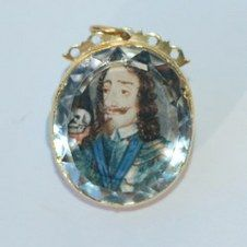 Stuart Crystal pendant - Charles I Ruled: 1625-1649 Circa 1650-1660  High-carat gold pendant, circa 1650 - 1660, set with a watercolor portrait on vellum under faceted crystal, a commemorative piece for Charles I.  The monarch is portrayed wearing the blue sash of the Order of the Garter, with a skull on a table by his left shoulder,  symbolizing his death.