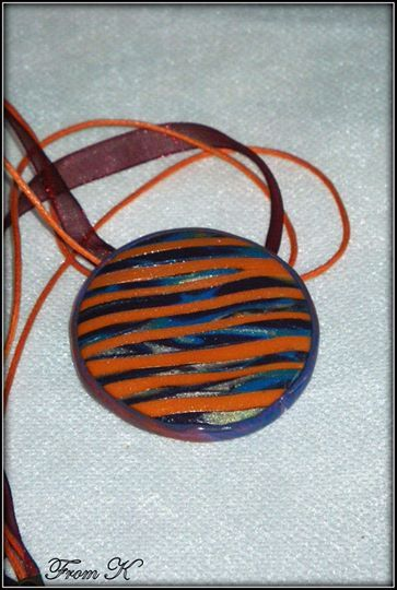 """Stripe polymer clay Necklace. Created by using the mokume cane technique with many layers of transitioning palettes. Featured colors are light blue, yellow, eggplant purple and the main fire orange (all in shimmer). Because each piece is handmade, every piece is completely unique and carries its own """"flaws"""" making it one-of-a-kind. About 4 cm in diameter. Finished with 41cm long ribbon and cotton cord with a lobster claw clasp. 20.00 Ron"""