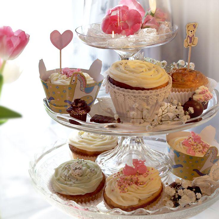Näyttävä muffini- tai kuppikakku torni syntyy päällekkäin kasatuista jalallisista kakkulautasista, jonka voi koristella leivonnaisten lisäksi esimerkiksi kukilla. helmillä ja pitsillä