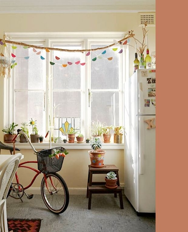 potted plants and a garland hanging off a branch-- the home of Nicole Valentine Don