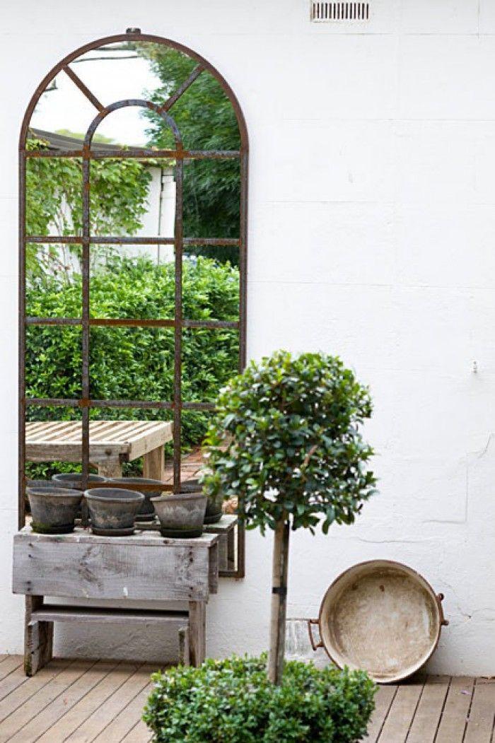Grote tuinspiegel tegen witte muur, verruimt de tuin.
