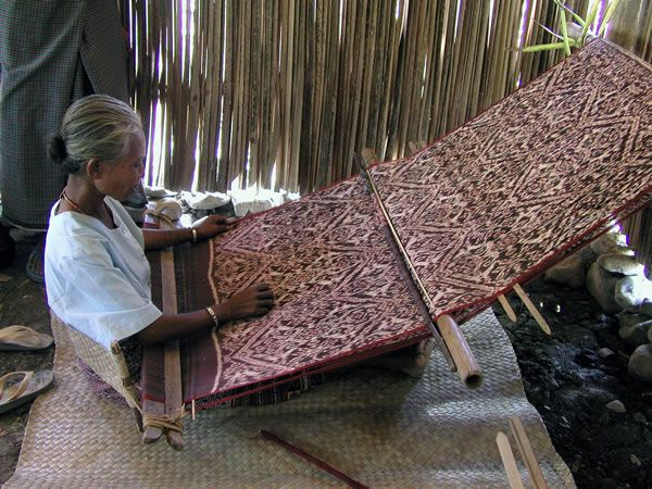 A weaver in Matabesi Biboki, West Timor. The weaver ties one end of her loom to a wall, a tree, or stakes driven into the ground, loops a strap or a wooden yoke behind her back, and leans forward and back to control the tension of her loom. If the tension is uneven, the cloth will slant as she weaves. Backstrap looms are portable and easy to store, and are often made at home.