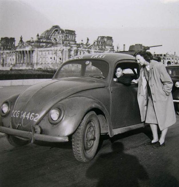 Great photo of a 1945 (me guessing) ish Volkswagen serving as a taxi, bombed out Reichstag building in the background
