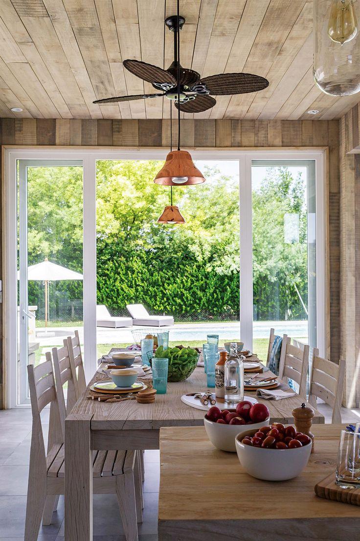 Quincho rústico y moderno con revestimiento de madera y ventanales hacia la pileta. En una casa de Nordelta decorada en base neutra.