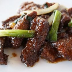 Mongolian Beef: 1 lb flank steak ¼ cup cornstarch 2 teaspoons vegetable oil ½ teaspoon ginger (minced) 1 tablespoon garlic (minced) ½ cup soy sauce 1/2 cup water ½ cup brown sugar 2 tablespoons rice wine ½ teaspoon red pepper flakes 2 green onions (sliced) 1 medium onion (sliced) Oil (for frying)