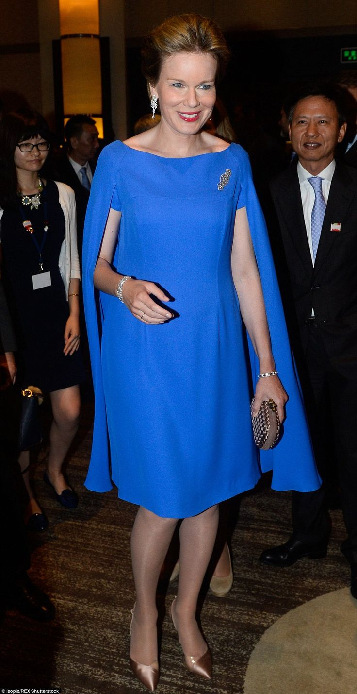Daring: Queen Mathilde wore a bright blue dress and matching cape to an evening reception in Shanghai...