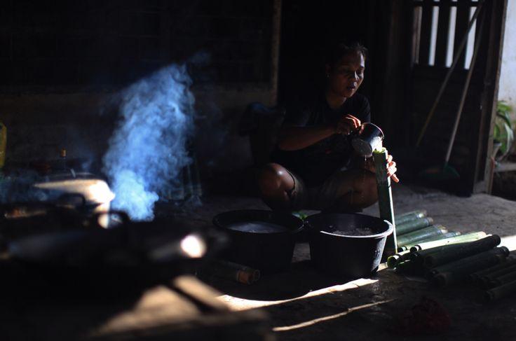 Ibu Johan membuat Nasi Bambu dengan mengisi Santan Kelapa ke Dalam Bambu yang sudah di isi dengan Beras, Desa Konda, Kendari, Sulawesi Tenggara, Indonesia